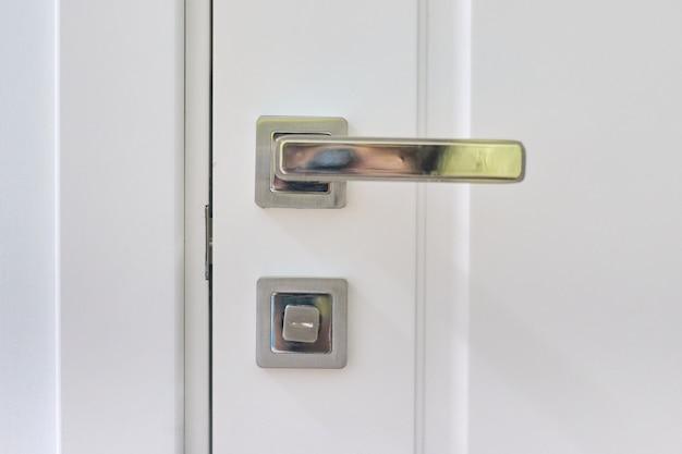 Perto da maçaneta da porta moderna de metal cromado em uma porta interior branca.