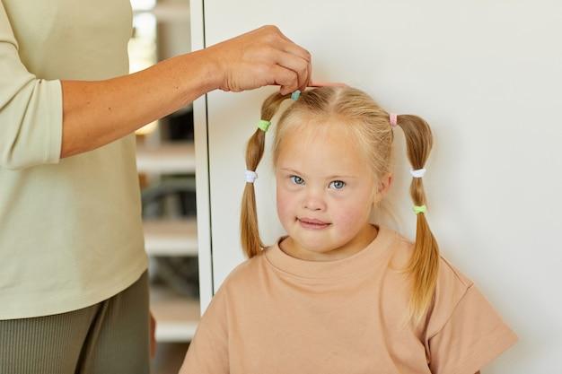 Perto da mãe carinhosa irreconhecível, penteando o cabelo de uma linda garota com síndrome de down e amarrando-o em tranças, copie o espaço