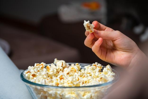 Perto da mão, acordando a pipoca de uma tigela enquanto assiste à tv. pessoa sentada em um sofá confortável e assistindo home cinema no escuro.