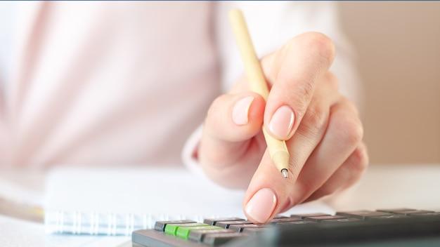 Perto da mão da mulher com calculadora, contando e fazendo anotações no caderno.