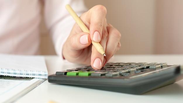 Perto da mão da mulher com calculadora, contando e fazendo anotações para o caderno. conceito de finanças, economia, tecnologia e pessoas. foco seletivo.