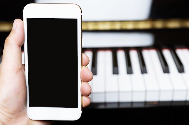 Perto da mão de pessoas segurando um telefone inteligente móvel branco com tela em branco vazia.