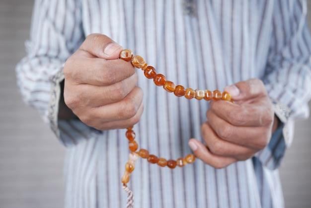 Perto da mão de um homem muçulmano com um rosário rezando no ramadã