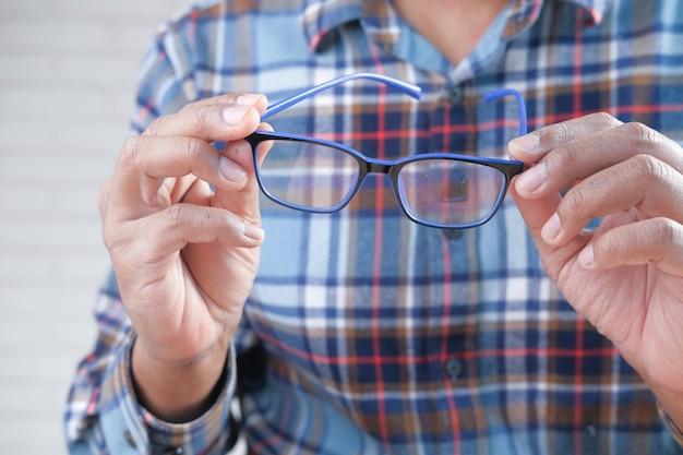 Perto da mão de um homem segurando um óculos no escuro