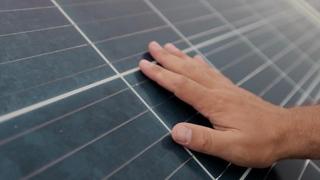 Perto da mão de um jovem engenheiro está verificando o funcionamento do sol e a limpeza dos painéis solares fotovoltaicos. conceito de ecologia. fazenda solar. conceito de energia limpa.