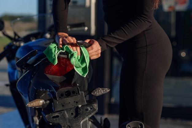 Perto da mão de uma jovem sedutora lavando uma motocicleta esportiva elegante e a limpa
