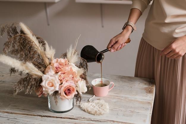 Perto da mão de uma jovem servindo café de uma moka em uma xícara - manhã, café da manhã, conceito de intervalo