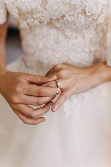 Perto da mão de uma mulher ajustando o anel de noivado.