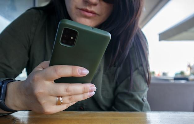 Perto da mão de uma mulher com o anel de casamento, segurando o celular ou o celular durante a pausa para o café. uma mulher com um vestido verde está lendo algo em seu smartphone enquanto está sentada em um café moderno.