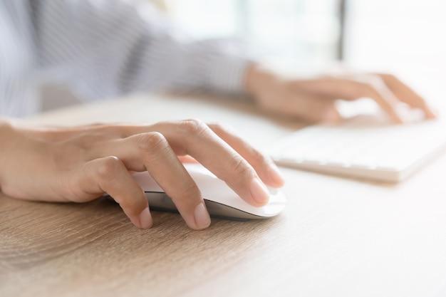 Perto da mão de uma mulher de negócios, digitando no teclado do computador com o mouse enquanto está sentado