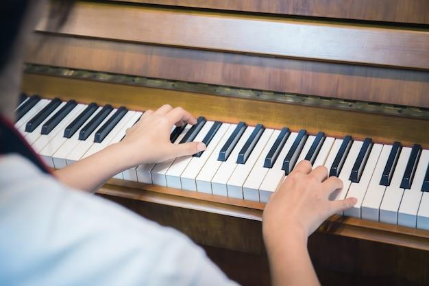 Perto da mão de uma mulher feliz tocando piano para relaxar.