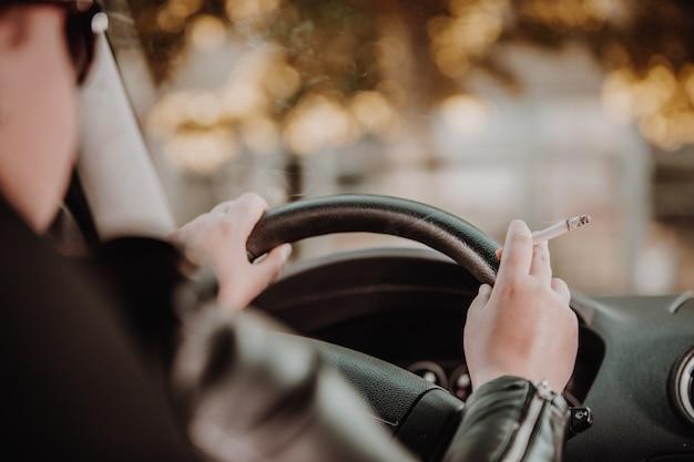 Perto da mão de uma mulher fumando cigarro dentro do carro enquanto dirige um veículo