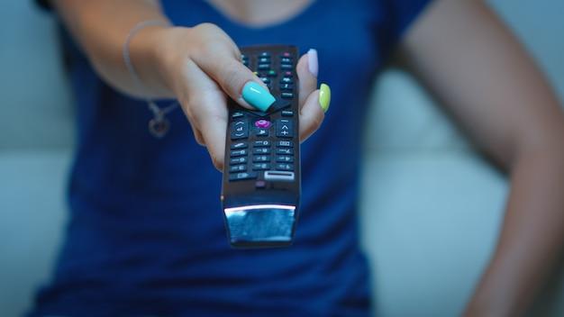 Perto da mão de uma mulher mudando os canais de tv, sentado no sofá. controle remoto da televisão nas mãos da senhora apontando a tv e escolhendo um filme, segurando o controle e pressionando o botão