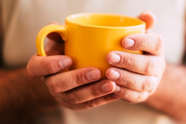 Perto da mão de uma mulher pegando uma grande xícara amarela de bebida quente como chá ou café