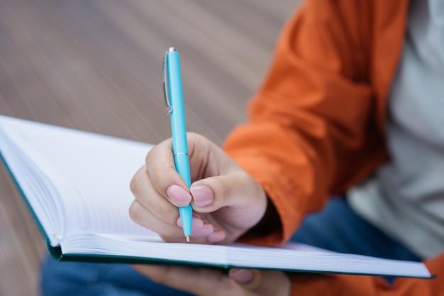 Perto da mão de uma mulher segurando uma caneta, fazendo anotações no bloco de notas, escrevendo o currículo do autor escrevendo um livro