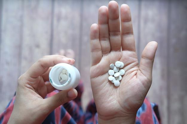 Perto da mão de uma mulher tomando pílulas