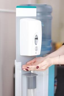 Perto da mão de uma mulher, usando o distribuidor automático de álcool para limpar as mãos no hospital.