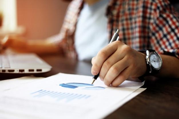 Perto da mão do homem de negócios trabalhando no computador laptop com o diagrama de informações do gráfico de negócios na mesa de madeira como conceito