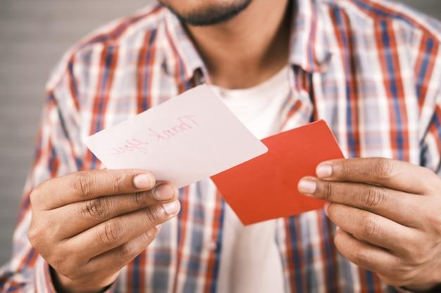 Perto da mão do homem lendo uma carta de agradecimento