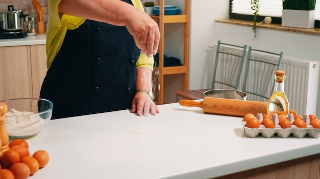 Perto da mão velha, peneirando a farinha de trigo na mesa da cozinha. padeiro sênior aposentado com avental, uniforme de cozinha, borrifando, peneirando e espalhando ingredientes refogados, assando pães e pizzas caseiras.