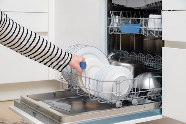 Perto da máquina de lavar louça de descarga manual na cozinha.