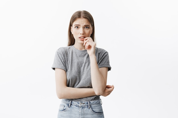 Perto da menina bonita estudante caucasiano com cabelos escuros na moda roupas cinza, segurando a mão perto da boca, com expressão de nojo não pode olhar para beijar par na rua.