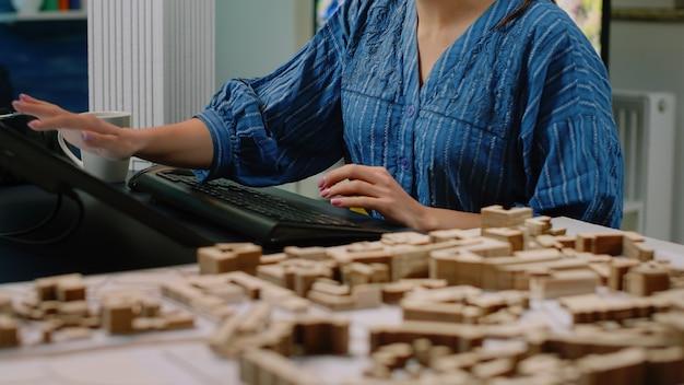Perto da mesa de arquitetura com o modelo de construção e o computador