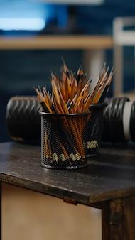Perto da mesa de madeira com lápis coloridos para artista