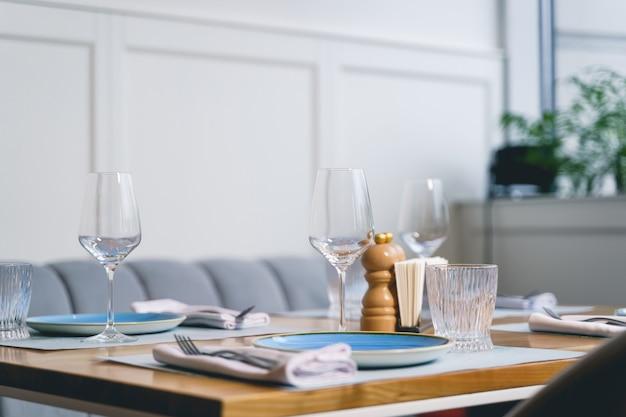 Perto da mesa de madeira com taças de vinho, pratos, garfos, guardanapos e copos no restaurante