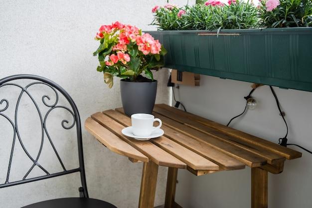 Perto da mesa de madeira com uma xícara de café na varanda. zona residencial de conforto