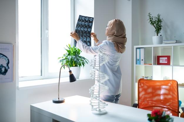Perto da mesa de trabalho. cientista médica usando lenço na cabeça, em pé perto da mesa de trabalho e olhando para o raio-x