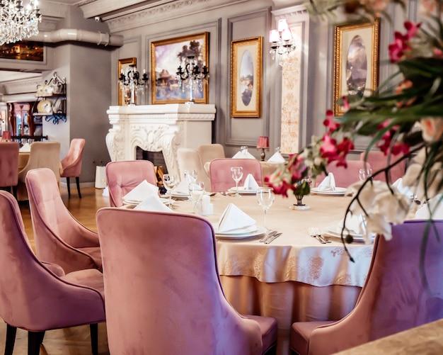 Perto da mesa do restaurante com cadeiras de veludo rosa no salão pintado cinza com pinturas clássicas
