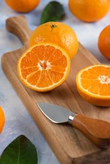 Perto da metade da tangerina cortada na tábua de madeira