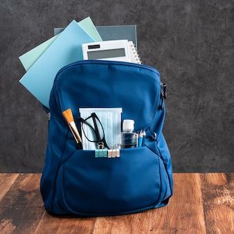 Perto da mochila azul com papelaria escolar, mesa de madeira e fundo preto, de volta ao conceito de design da escola.