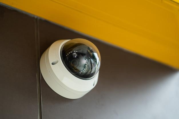 Perto da moderna câmera cctv em uma parede. conceito de vigilância e monitoramento.