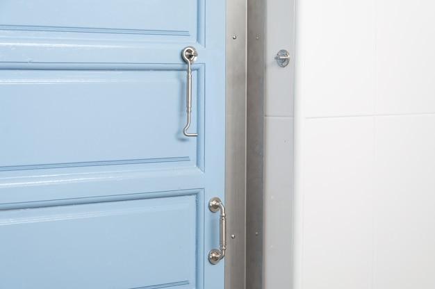 Perto da moderna porta e maçanetas azuis em casa