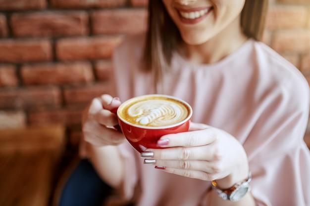 Perto da morena sorridente com os olhos fechados, vestido elegante, desfrutando de café na cafeteria