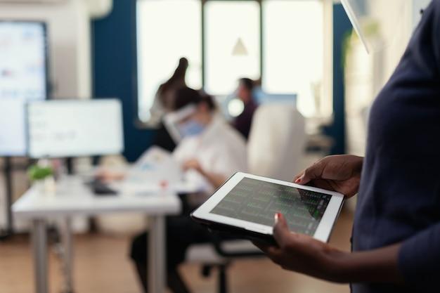 Perto da mulher africana segurando e usando o tablet pc no local de trabalho. colegas de trabalho multiétnicas respeitando a distância social em empresas durante a pandemia global de coronavírus.