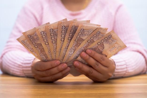 Perto da mulher asiática com calculadora contando dinheiro. mulher calcular os gastos em casa.