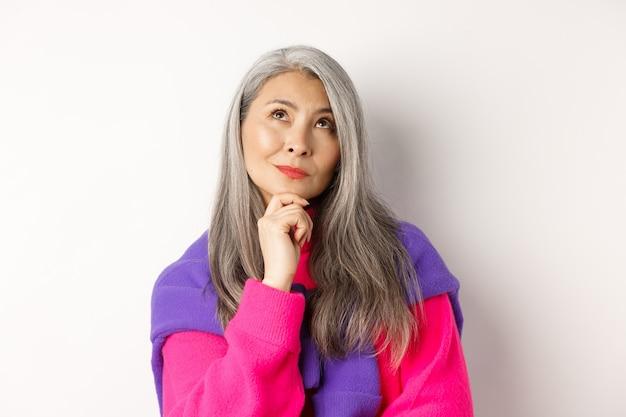 Perto da mulher asiática pensativa com cabelo grisalho, olhando para cima e pensando, tomando decisão, em pé sobre um fundo branco.