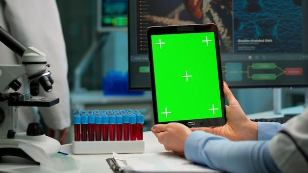 Perto da mulher cientista segurando o tablet com maquete verde em laboratório equipado moderno. equipe de microbiologistas fazendo pesquisa de vacina, escrevendo no dispositivo com chroma key, display isolado.