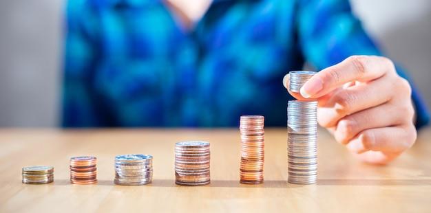 Perto da mulher de negócios de sucesso segurar a moeda e economizar dinheiro para o plano de crescimento do investimento com o conceito de planejamento econômico e do investidor da moeda
