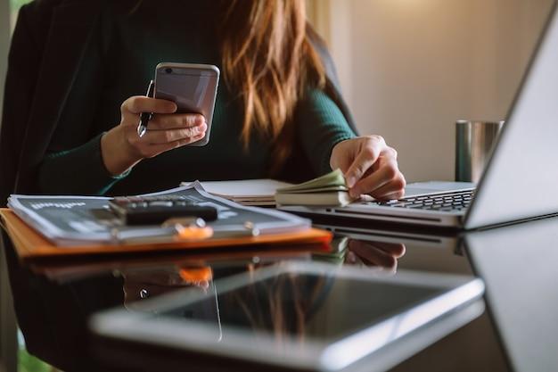Perto da mulher de negócios ou contador mão segurando a caneta trabalhando na calculadora para calcular na mesa sobre o custo no escritório em casa.