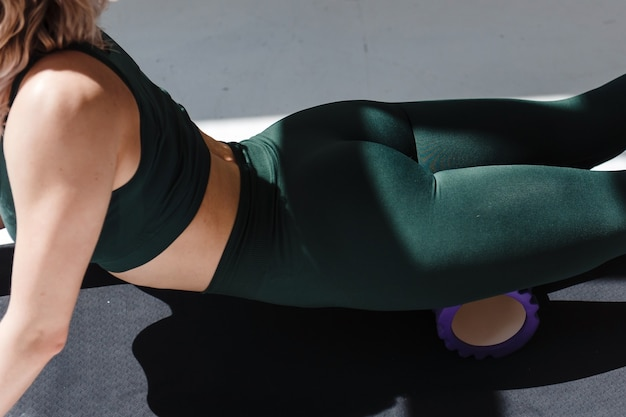 Perto da mulher fitness com roupas esporte verde, usando o rolo de espuma para relaxar os músculos após o exercício matinal. jovem garota fazendo massagem para as pernas na sala branca.