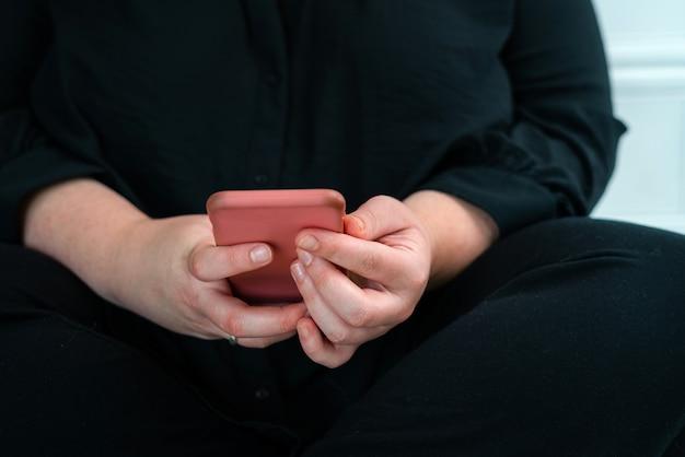 Perto da mulher lendo notícias no telefone inteligente em casa. mensagens de texto de mãos ou rolagem nas redes sociais. navegar na internet, bater papo online