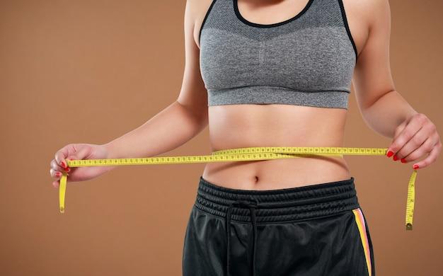 Perto da mulher magra, medindo o tamanho da cintura com fita métrica. isolado em fundo amarelo.