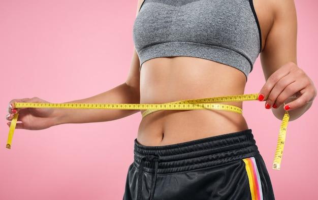 Perto da mulher magra, medindo o tamanho da cintura com fita métrica. isolado em fundo rosa.