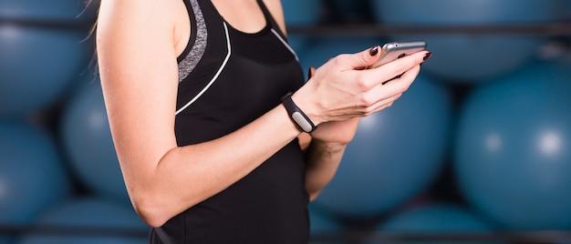 Perto da mulher usando o celular e o rastreador de fitness no ginásio.