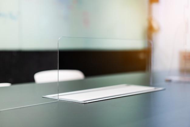 Perto da parede divisória do separador de acrílico plexiglass com passagem na mesa da sala de reuniões.