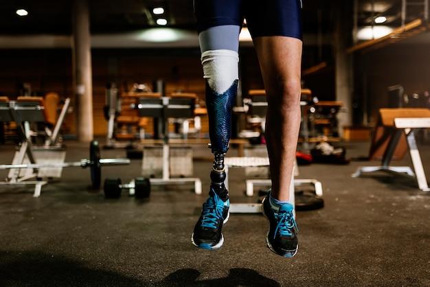 Perto da perna da prótese de jovem treinando no ginásio. conceito de desportista com deficiência.